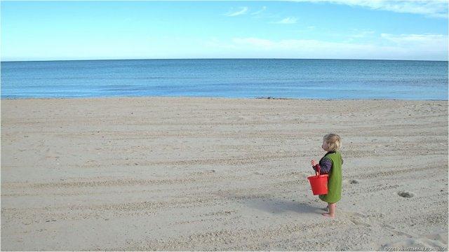 Niña con cubo en la playa