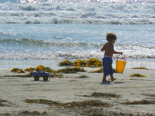 Niño con cubo y camion en la playa